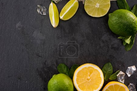 Photo for Lime and orange slices with mint leaves and ice on stone board, barman cocktail background - Royalty Free Image