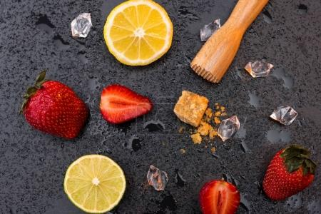 wooden squeezer with lemon and strawberries