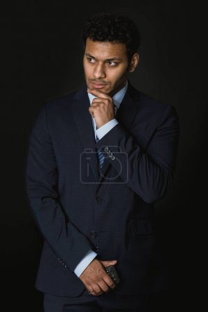 Photo for Young pensive african american businessman standing isolated on black - Royalty Free Image