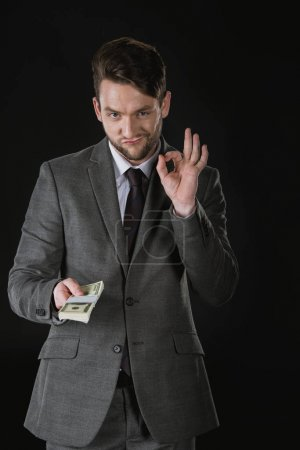 Photo for Young businessman holding dollar banknotes and showing ok sign isolated on black - Royalty Free Image