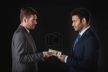 Photo pour Homme d'affaires donnant de l'argent et soudoyant partenaire d'affaires isolé sur noir - image libre de droit