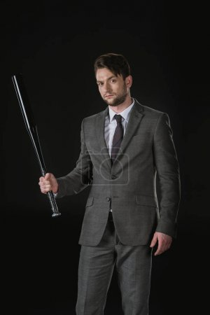 Serious businessman with bat