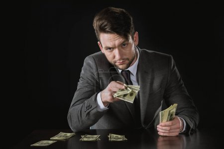 Photo for Portrait of businessman sitting at table and holding money isolated on black - Royalty Free Image