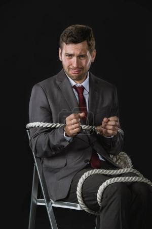young businessman roped on to chair
