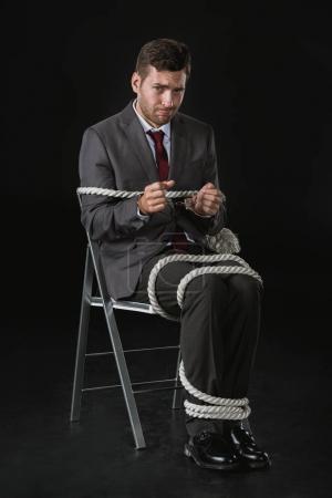 Foto de Joven empresario molesto cuerdo al Presidente aislado en negro - Imagen libre de derechos