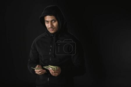 Photo for Young african american robber in zoodie holding money isolated on black - Royalty Free Image