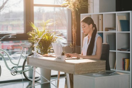 Photo for Concentrated attractive asian businesswoman working with laptop at workplace in office, bicycle standing behind - Royalty Free Image
