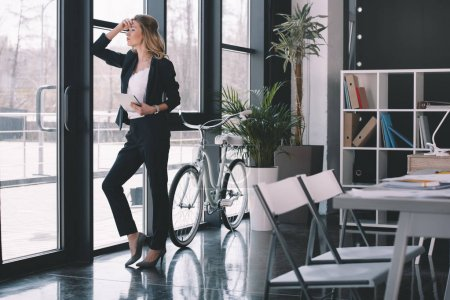 Photo for Attractive pensive businesswoman in suit with digital tablet standing at window in office, bicycle standing behind - Royalty Free Image