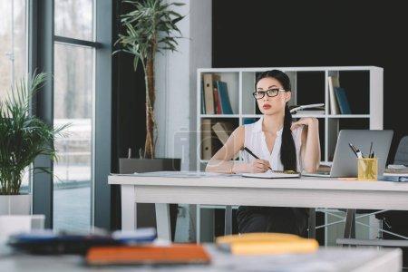 Photo pour Séduisante femme d'affaires asiatique travaillant avec ordinateur portable au lieu de travail au bureau - image libre de droit