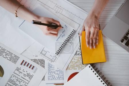 Photo pour Recadrée et vue du dessus de femme d'affaires travaillant et écrivant dans le bloc-notes au travail - image libre de droit