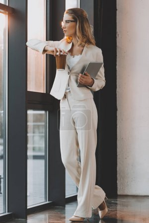 Photo for Attractive pensive businesswoman in white suit with digital tablet and coffee standing at window in office - Royalty Free Image