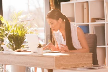 Photo pour Concentré de séduisante femme d'affaires asiatique travaillant avec ordinateur portable au lieu de travail au bureau - image libre de droit