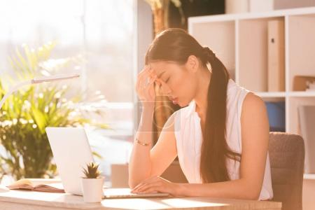 Photo for Tired asian businesswoman with headache sitting at workplace with laptop - Royalty Free Image