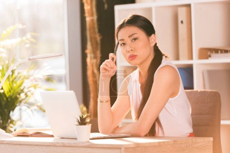 Photo for Pensive attractive asian businesswoman with laptop thinking and looking at camera in office - Royalty Free Image