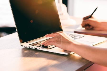 Photo pour Recadrée vue de femme d'affaires travaillant avec ordinateur portable au lieu de travail au bureau - image libre de droit