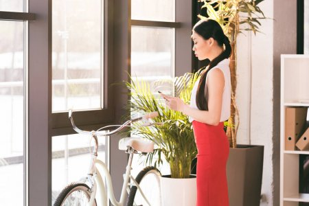Photo for Attractive asian businesswoman working with smartphone in office, bicycle standing behind - Royalty Free Image