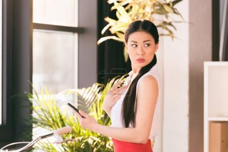 Photo pour Séduisante femme d'affaires asiatique travaillant avec smartphone et permanent au bureau - image libre de droit