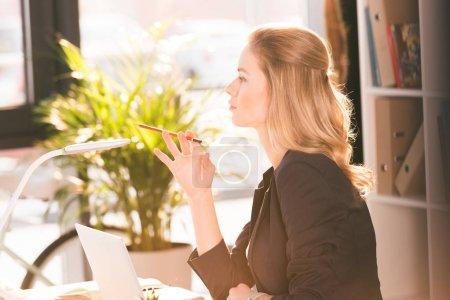 Photo pour Vue latérale de belle jeune femme tenant crayon et regardant loin tout en utilisant un ordinateur portable - image libre de droit