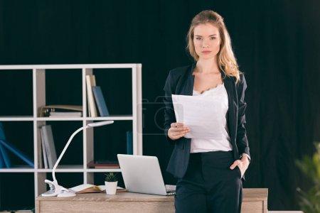 Photo pour Confiant jeune femme d'affaires avec la main dans la poche tenant du papier et regardant la caméra - image libre de droit