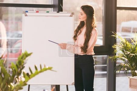 Photo pour Jeune femme d'affaires professionnelle faisant la présentation et pointant vers le tableau blanc vierge - image libre de droit