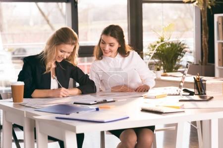 Photo pour Sourire des jeunes femmes d'affaires, travaillant ensemble à table avec ordinateur portable - image libre de droit