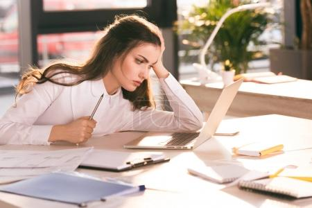 Photo for Tired young businesswoman holding pencil and looking at laptop at workplace - Royalty Free Image