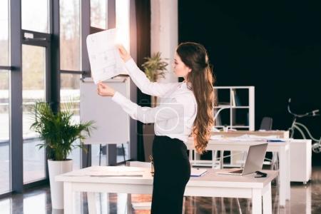 Photo pour Vue latérale d'une femme d'affaires ciblée, analyse de documents dans le bureau moderne - image libre de droit