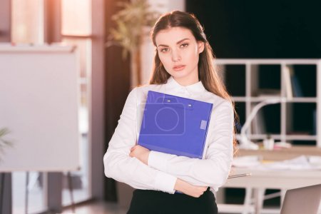 Photo for Portrait of businesswoman holding clipboard while standing in modern office - Royalty Free Image