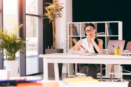 Photo pour Femme d'affaires asiatique grave assis au milieu de travail et travaillant dans les bureaux modernes - image libre de droit