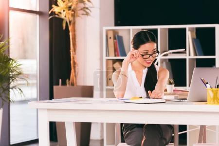 Photo pour Femme d'affaires asiatique souriant assis au milieu de travail et travaillant dans les bureaux modernes - image libre de droit