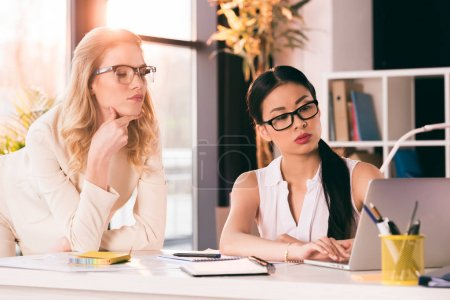 young multiethnic businesswomen looking at laptop