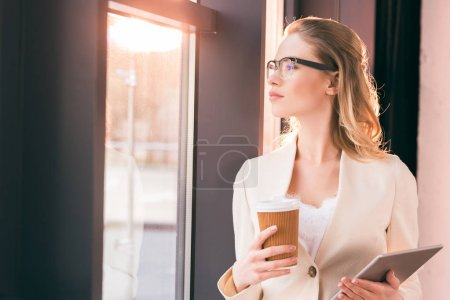 Photo for Young businesswoman in glasses standing and holding digital tablet and coffee cup - Royalty Free Image