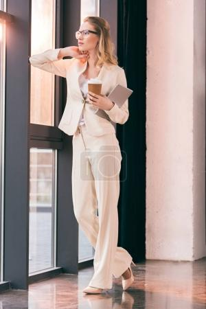 Photo for Young businesswoman in suit standing in office and holding digital tablet and coffee cup - Royalty Free Image