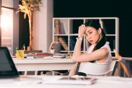 Photo for Pensive young asian businesswoman sitting at table in office and looking at camera - Royalty Free Image