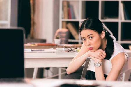 Foto de Joven empresaria asiática pensativa sentado en la mesa en la oficina y mirando a cámara - Imagen libre de derechos
