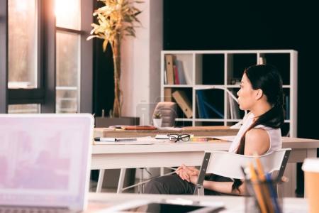 Foto de Joven empresaria asiática sentada a la mesa en la oficina y mirando a un lado - Imagen libre de derechos