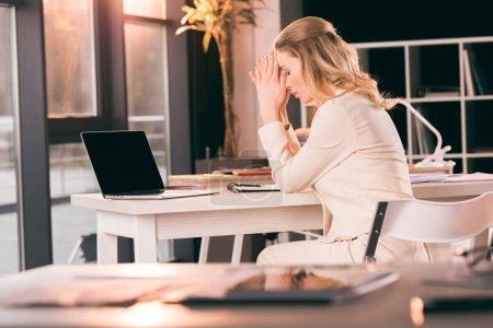 upset businesswoman sitting at office