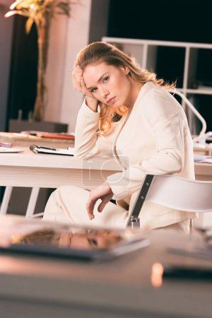 Photo for Young tired businesswoman sitting at table in office and looking at camera - Royalty Free Image