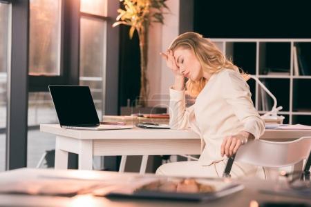 Foto de Joven mujer de negocios cansada en traje sentado en la mesa en la oficina - Imagen libre de derechos