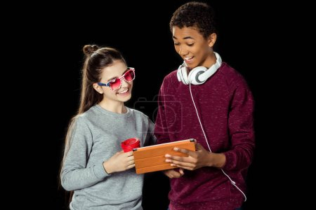 Teen couple looking at tablet