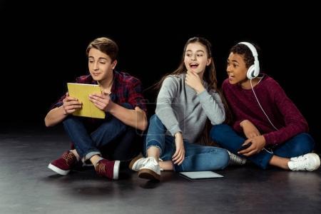 teenagers looking at friend using tablet