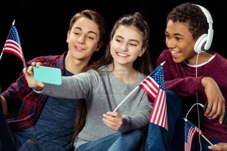 Photo pour Heureux groupe d'adolescents prendre selfie avec Etats-Unis drapeau isolé sur noir - image libre de droit