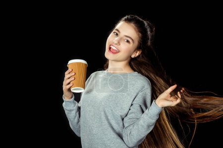 Photo for Happy teen girl with cup of coffee to go isolated on black - Royalty Free Image