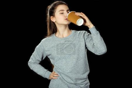 Photo for Teen girl drinking coffee to go isolated on black - Royalty Free Image