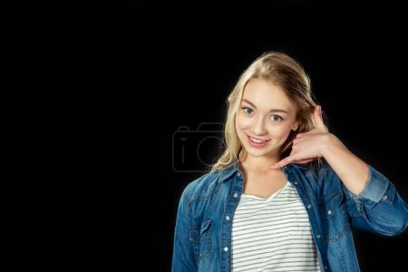 Photo for Smiling teen girl doing call me gesture isolated on black - Royalty Free Image