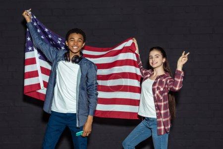 Photo pour Heureux couple teen avec drapeau usa sur fond noir - image libre de droit