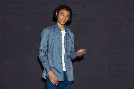 Photo for Teen boy listening music with headphones and smartphone on black - Royalty Free Image