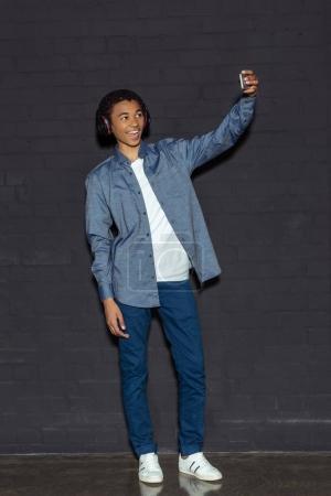 boy in headphone taking selfie