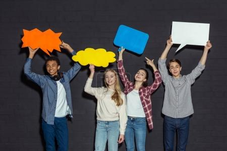Photo for Group of teenagers holding blank speech bubbles over heads on black - Royalty Free Image