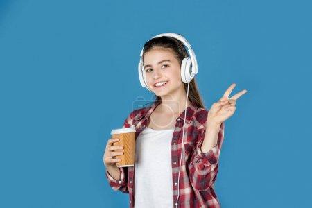 teen girl in headphones with coffee